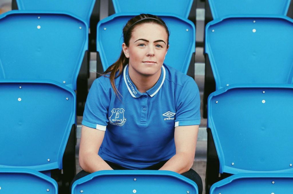 Simone is sitting in the centre of the photo on blue chairs at Everton's stadium, 古迪逊公园