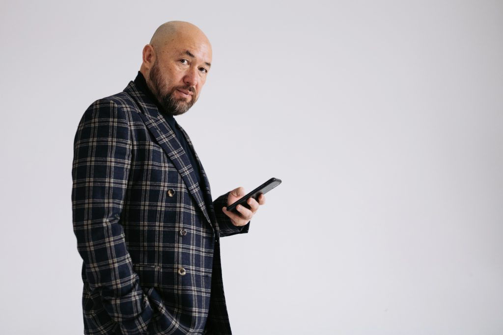 A picture of Russian director Timur Bekmambetov who is wearing a check jacket and using a smart phone.