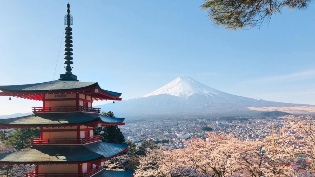 A view of Japan, featuring blossom trees, a traditional, Japanese pagoda building and distant, snow-capped mountain.