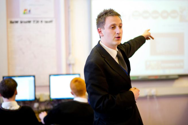 A trainee teacher addresses pupils during an IT lesson in a secondary school classroom.