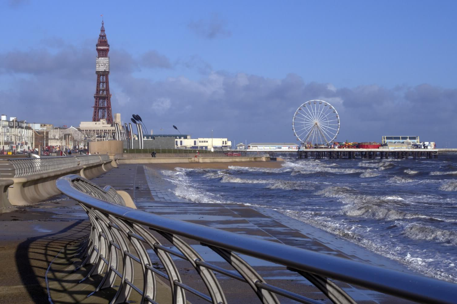 Waves come into sh要么e on the beach at Blackpool, with the skyline dominated by the iconic 布莱克浦 Tower.