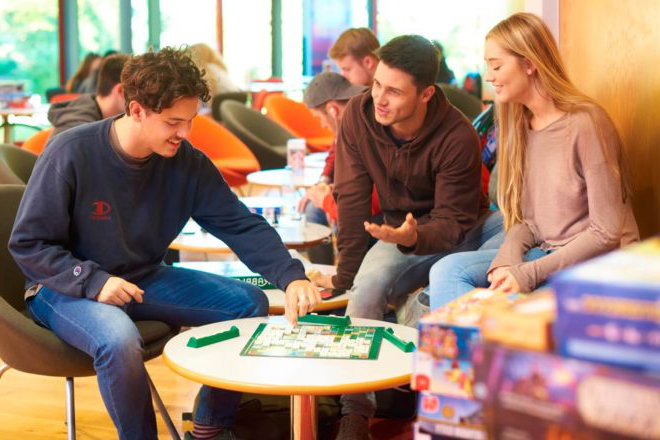 Three students play a board game at the Games Cafe in the Red Bar in the Arts Centre.