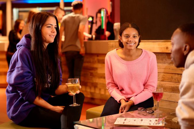 Three students chat over drinks in the SU Bar.