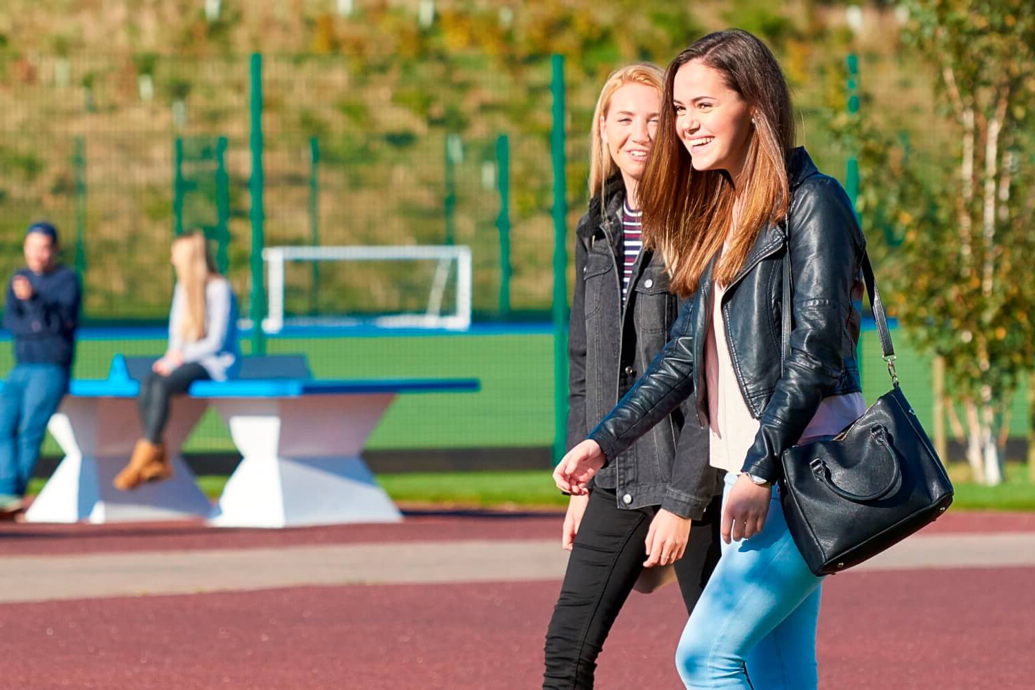 Two students walk past sports pitches and outdoor table tennis tables on campus.
