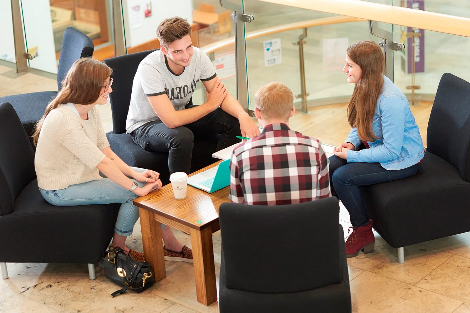Four students chat while sat round a table outside the Students' Union offices in the Hub.