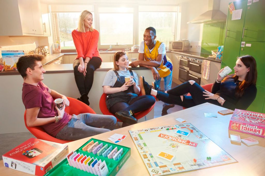 Five students chat in the kitchen and communal area of a halls of residence while drinking from mugs, with Monopoly and other board games on the table alongside them.