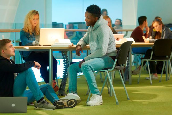 Students sit around tables in a social learning area on the first floor of the Tech Hub.