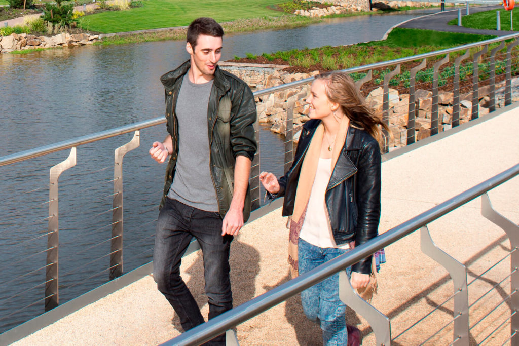 Two students walk across a bridge over a lake on the eastern side of the campus.