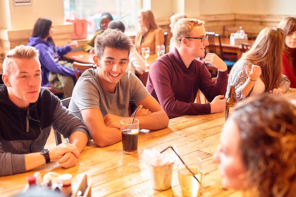 Students chat while sat around a table in the SU Bar.