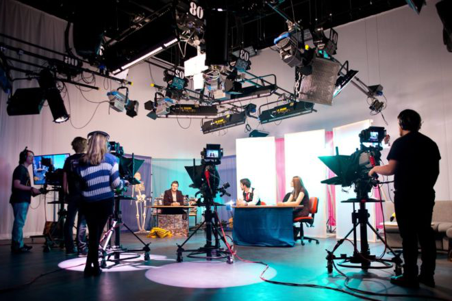 Students operate cameras and film presenters recording in the TV studio in Creative Edge.