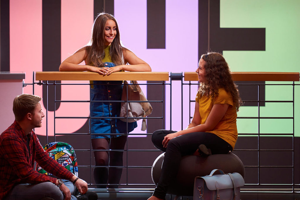 Three students chatting in the foyer of the Arts Centre, with EHU illuminated in large letters on the wall behind them.