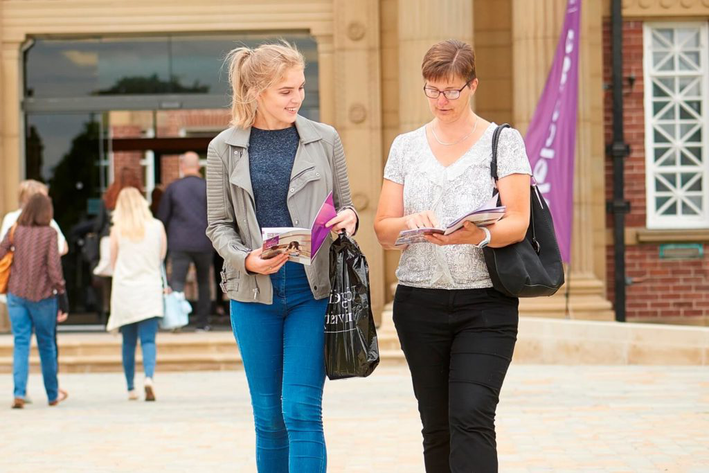 A mother and daughter look through printed guides as they walk away from the Main Building after attending an open day.