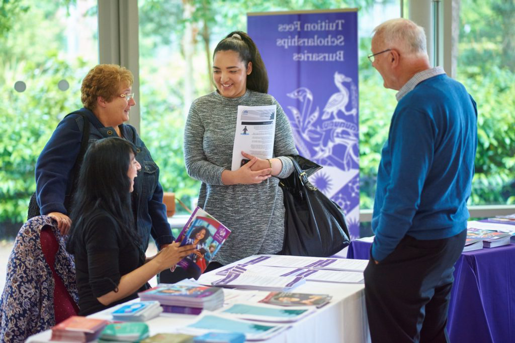 A prospective student and her parents speak with a member of the Money Advice team at an open day.