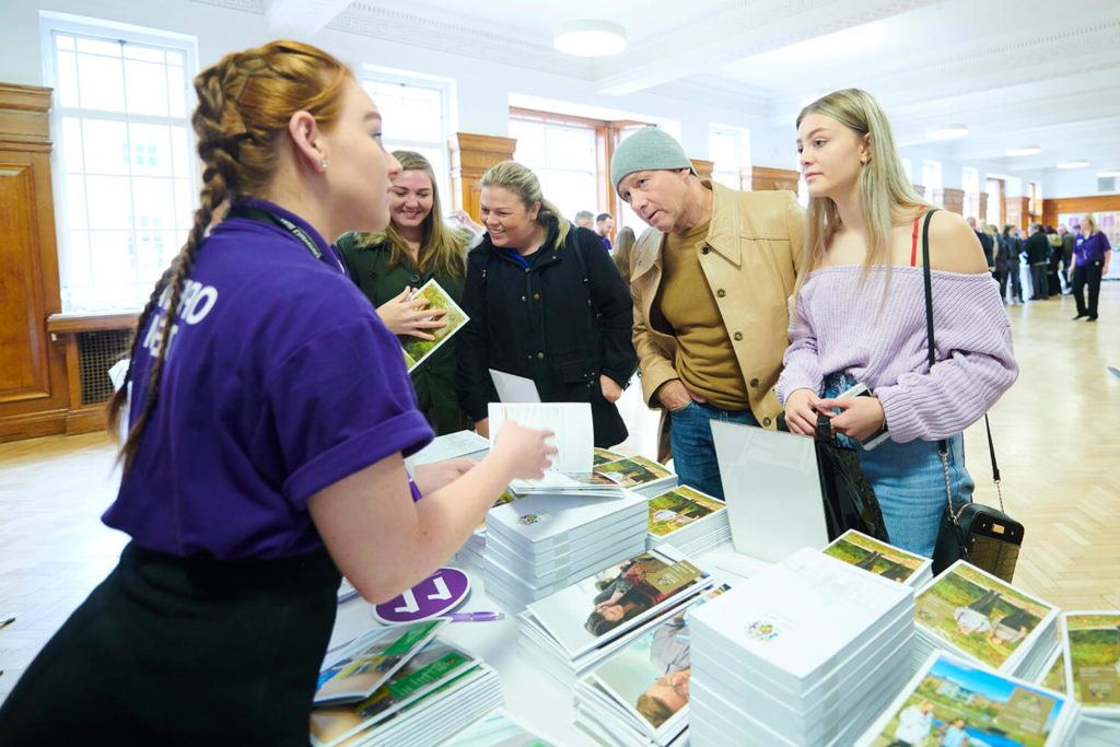 A student and her father speak to a member of the Open Day team at a stand in Sages Restaurant during an event.