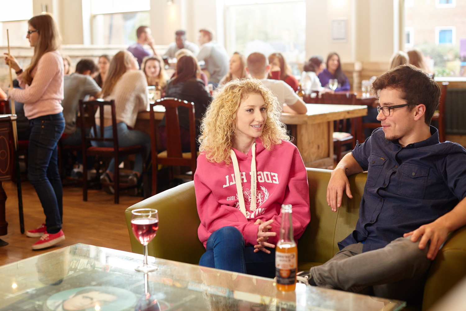 Two students chat over drinks while relaxing on a sofa in the SU Bar.