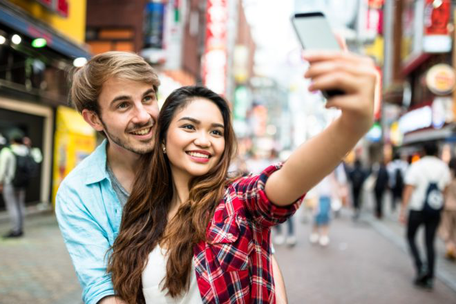 Two students pause to take a selfie in a busy street in Asia.