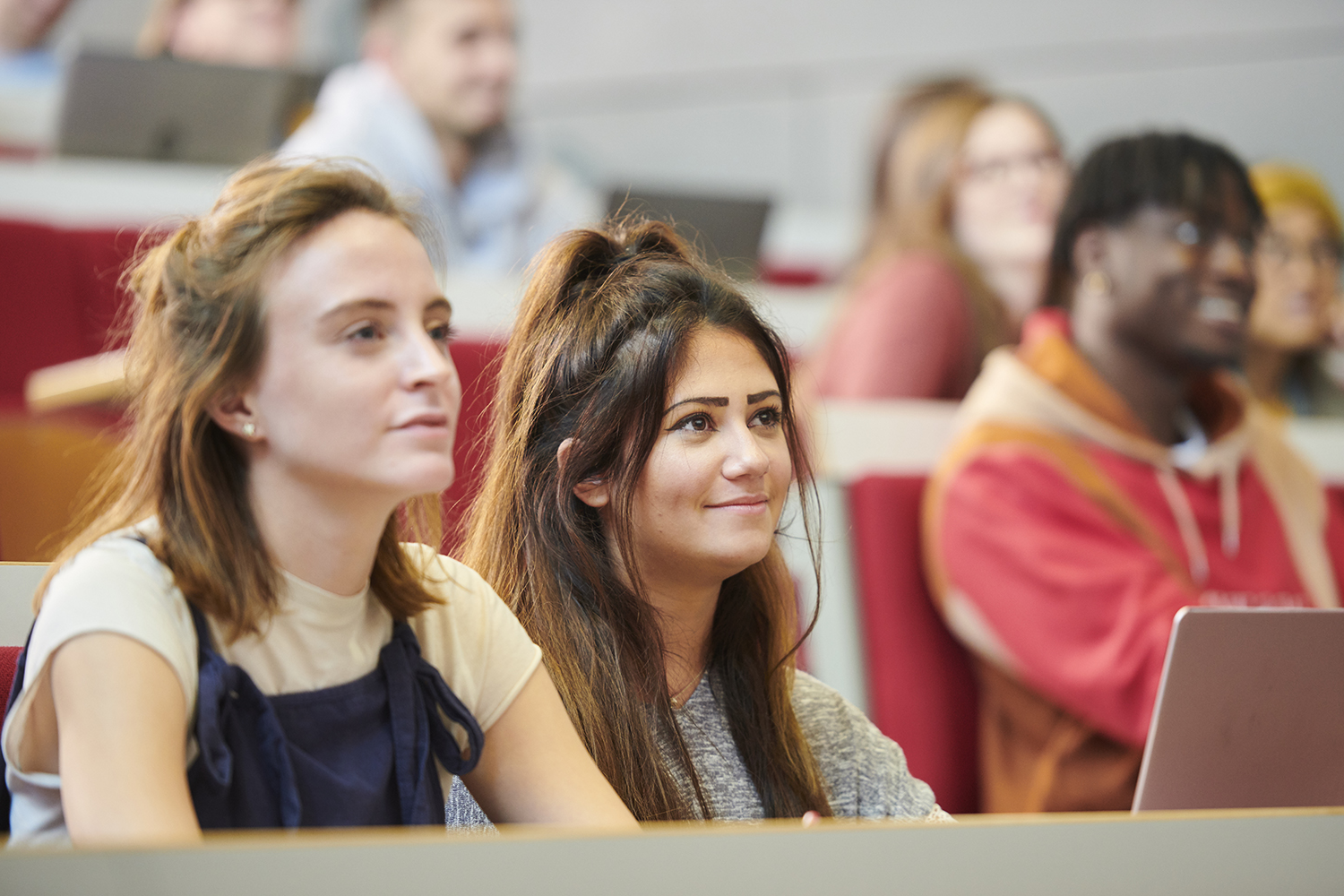 Two students sitting in a lecture theatre.